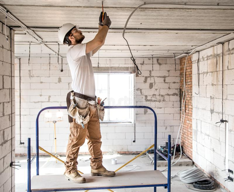Electrician installer with a tool in his hands, working with cable on the construction site stock images