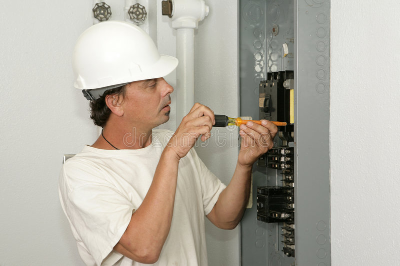 Electrician Installing Breaker. An electrician installing a breaker in an electric panel. Model is an actual electrician and all work is being performed stock photos
