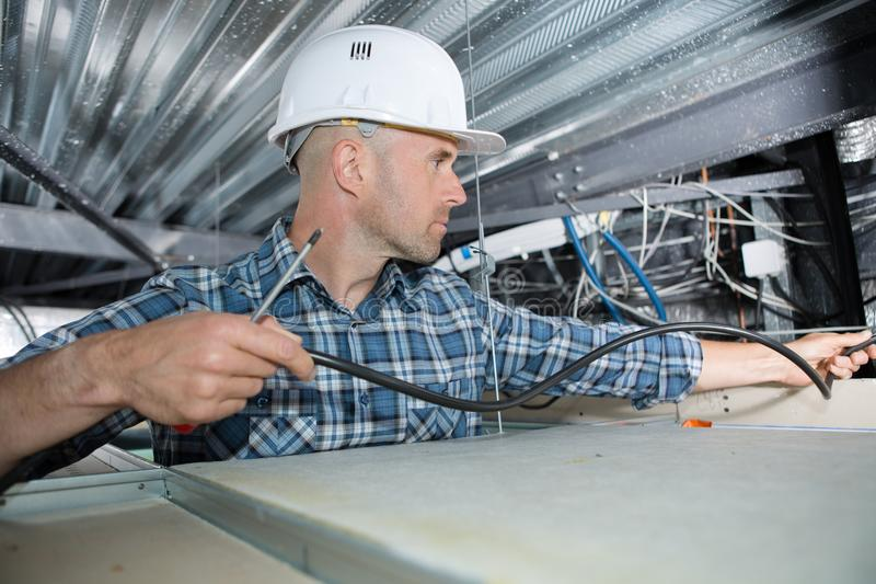 Electrician installing cable in roof space stock photos