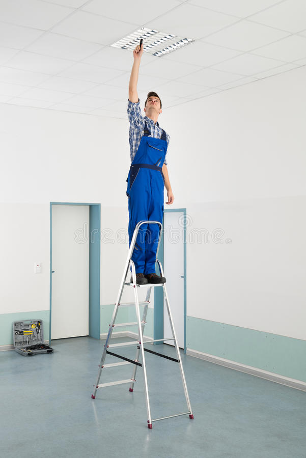 Electrician Installing Ceiling Light royalty free stock photos