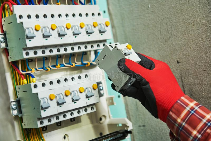 Electrician works in switchbox. current breaker installation. Electrician installing circuit current breaker equipment at electrical fusebox or switch box stock image