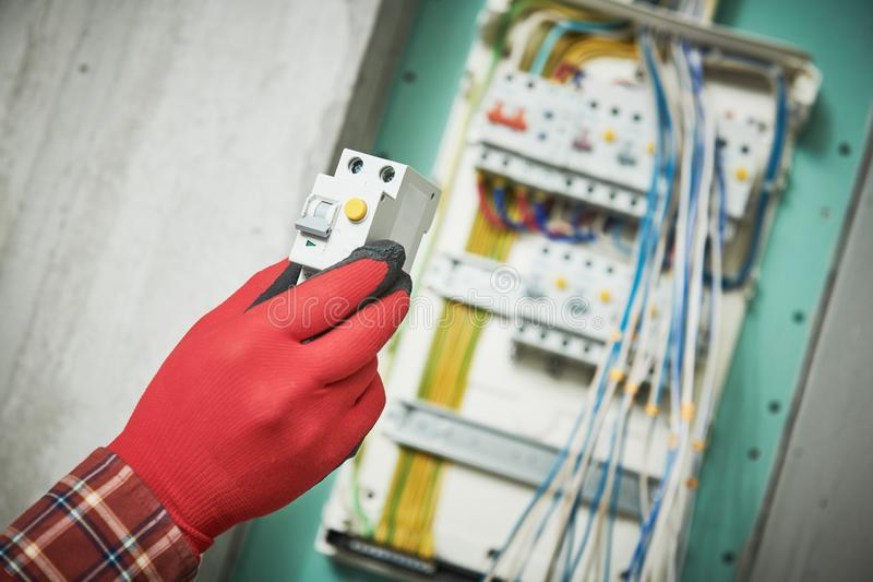 Electrician works servece. Hands with circuit breacker in front of switchbox stock image