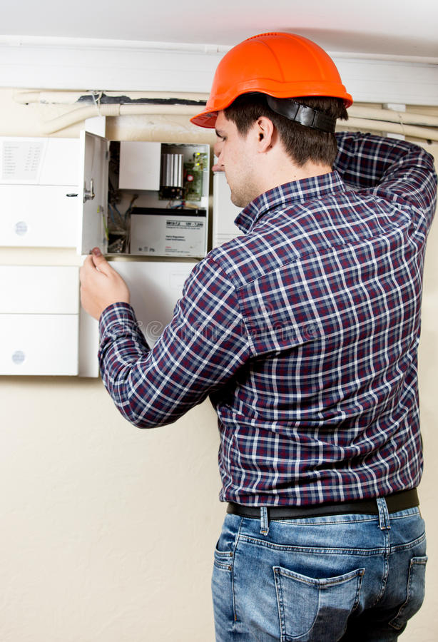 Electrician installing components in electrical shield royalty free stock image