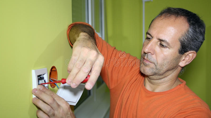 Electrician Installing an Electrical Switch. Electrician installing new light switch royalty free stock photo