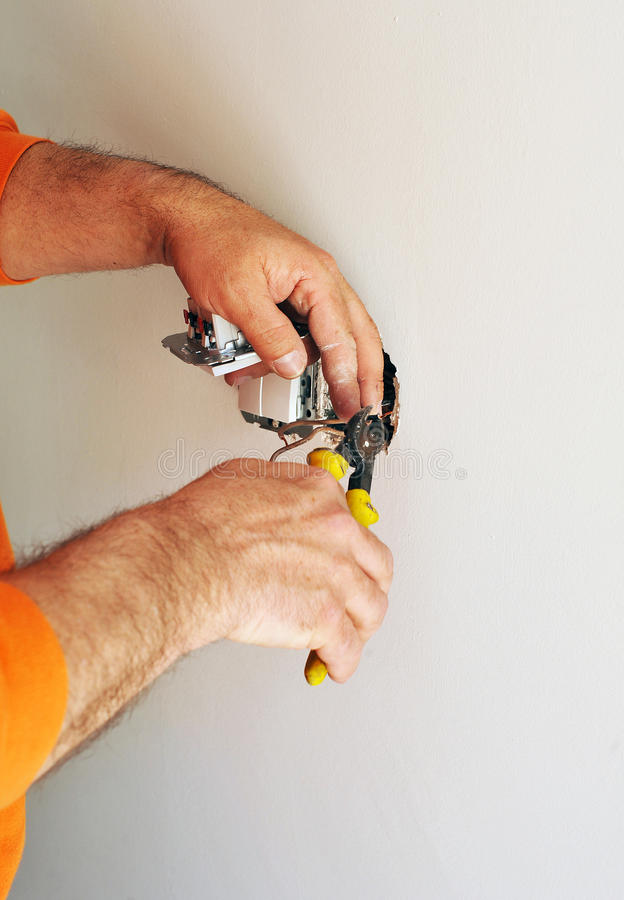 Electrician installing electrical switches in the new house. A qualified electrician cutting the wires with pliers to place white electric switches for the royalty free stock images