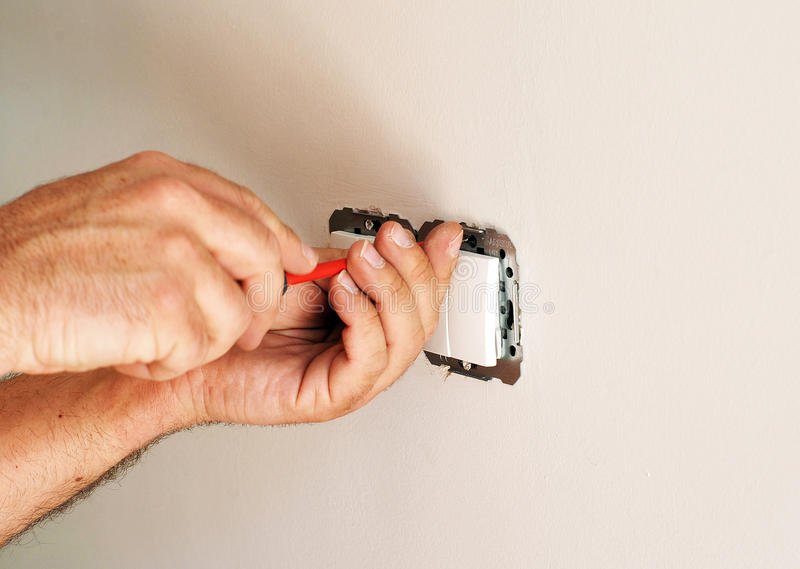 Electrician installing electrical switches. A qualified electrician placing white electrical switches during the renovation of the house stock images