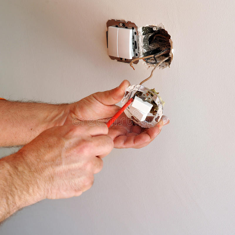 Electrician installing electrical switches. A qualified electrician placing white electrical switches during the renovation of the house royalty free stock image