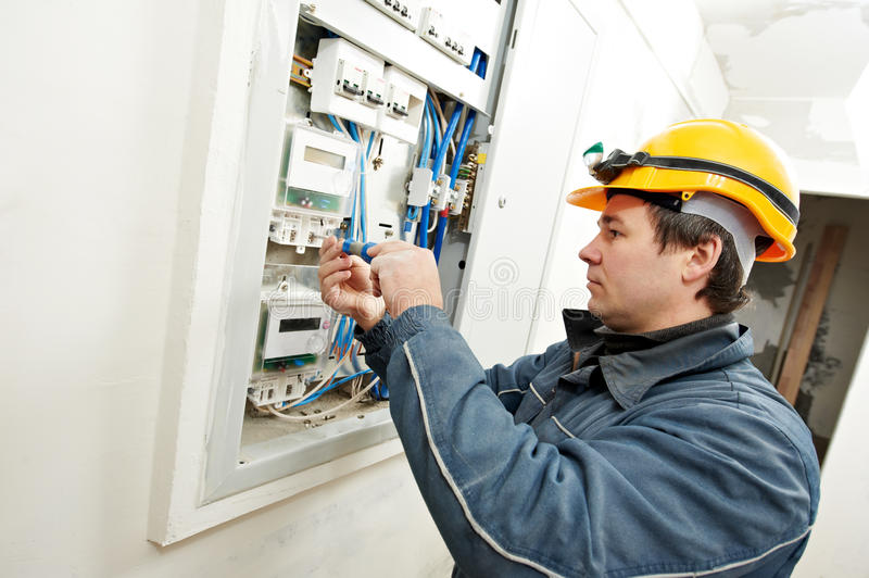 Electrician installing energy saving meter. One electrician builder at work installing energy saving meter into electric line distribution fuseboard stock images