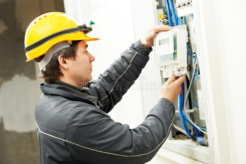 Electrician installing energy saving meter. Electrician builder at work installing energy saving meter into electric line distribution fuseboard royalty free stock photo