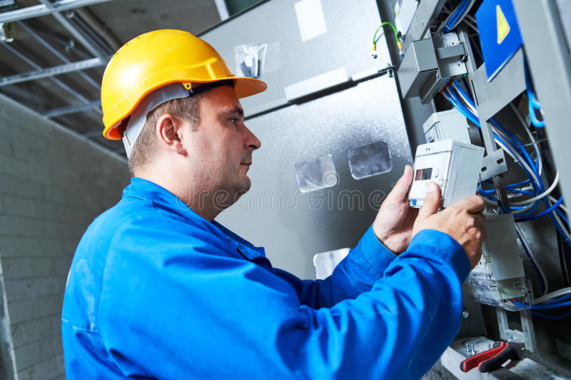 Electrician installing energy saving meter. Into switch box panel stock image