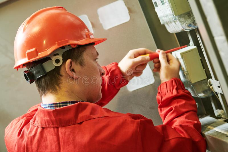 Electrician installing or repairing energy saving meter. Maintenance service royalty free stock image