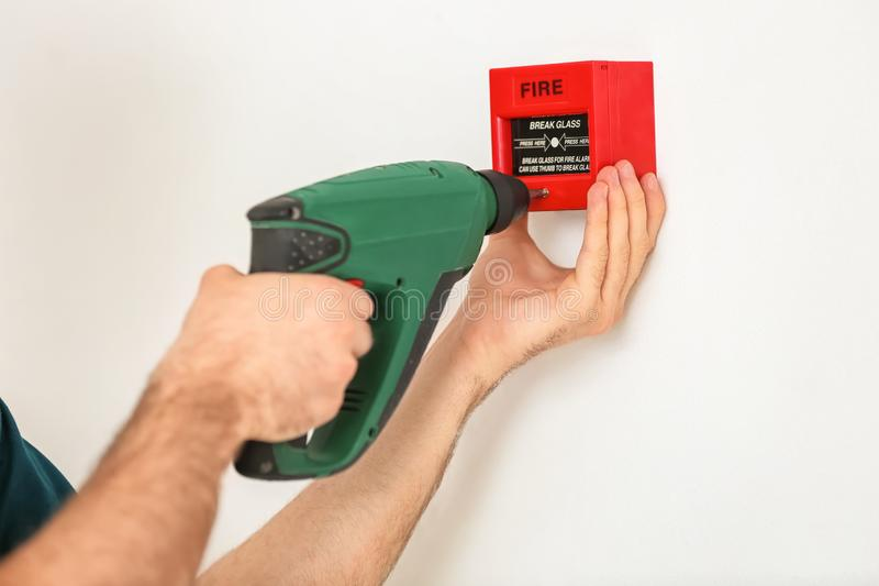 Electrician installing fire alarm on wall royalty free stock photos