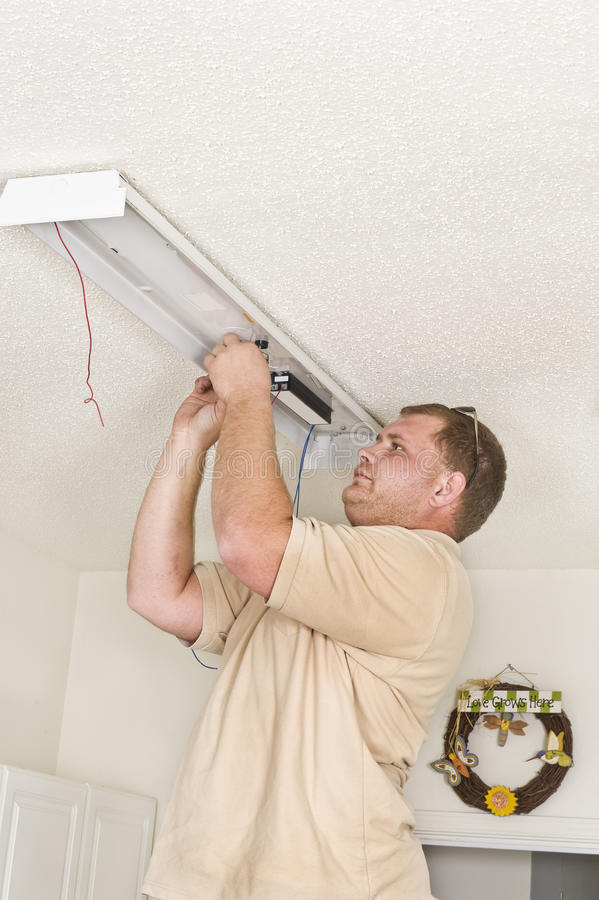Electrician Installing Fluorescent Lighting ballast stock images