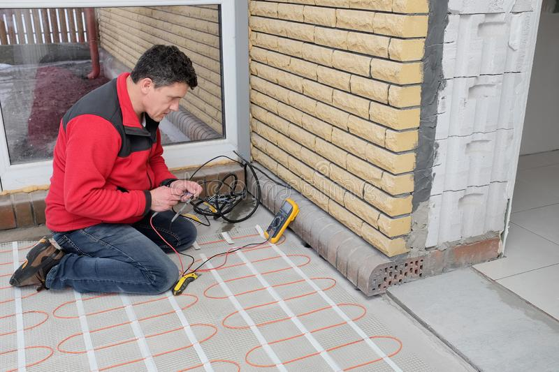 Electrician installing heating electrical cable on concrete floor. Man checking resistance of cable. Energy-saving technologies for home comfort royalty free stock photography