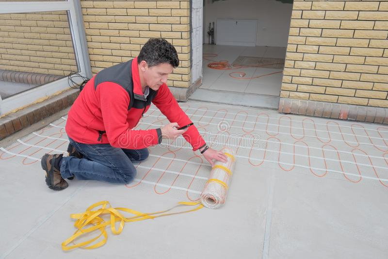 Electrician installing heating electrical cable on concrete floor. Man read instruction. On screen mobile phone. energy-saving technologies for home comfort royalty free stock images