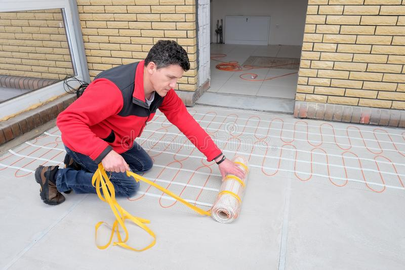 Electrician installing heating electrical cable on concrete floor. Man remove adgesive tape. Energy-saving technologies for home comfort stock photo