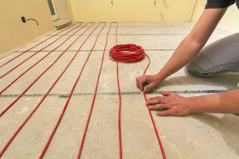 Electrician installing heating red electrical cable wire on cement floor in unfinished room. Renovation and construction, royalty free stock image