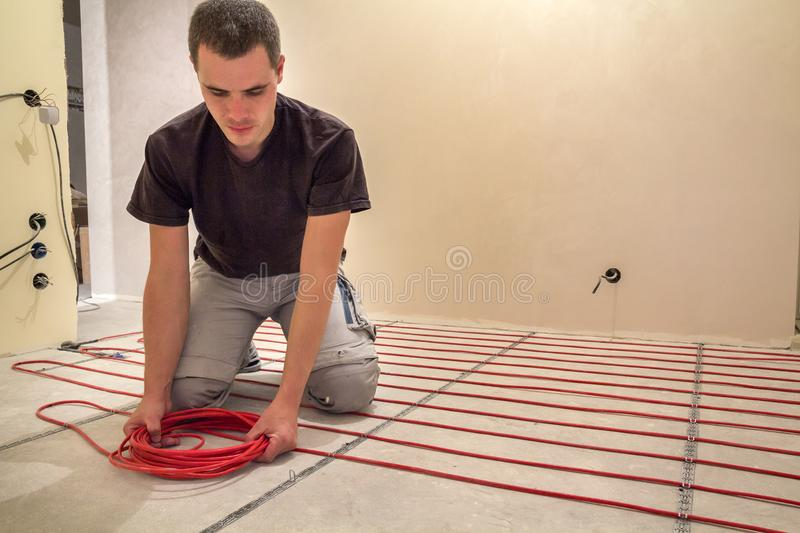 Electrician installing heating red electrical cable wire on cement floor in unfinished room. Renovation and construction, royalty free stock images