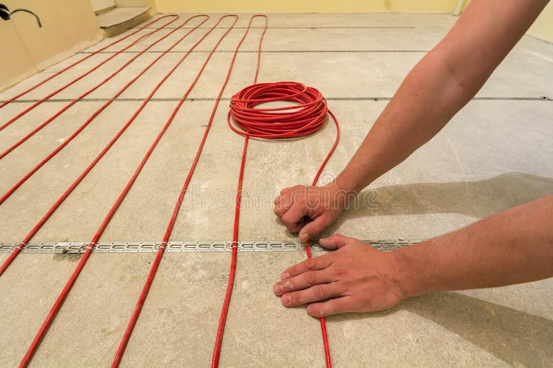 Electrician installing heating red electrical cable wire on cement floor in unfinished room. Renovation and construction,. Comfortable warm home concept royalty free stock photo