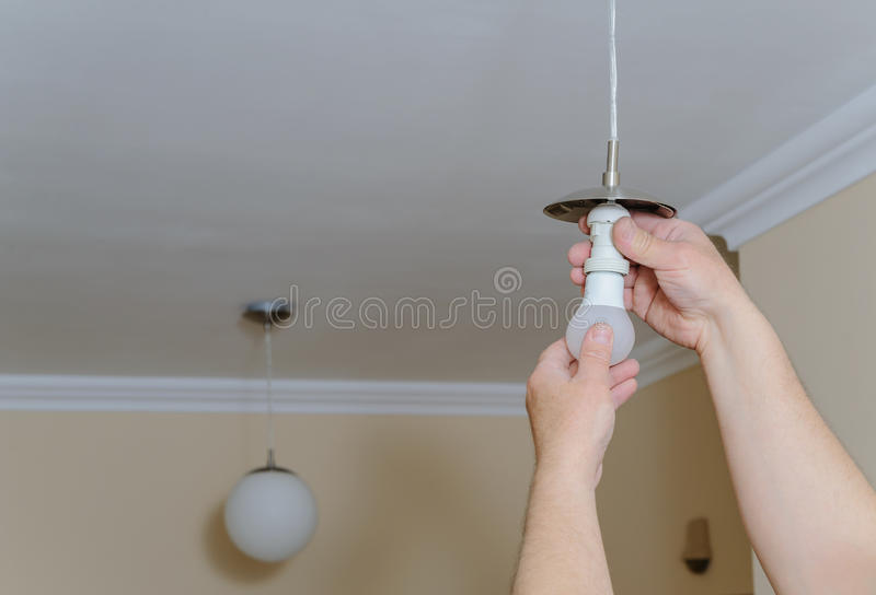 Electrician is installing a LED bulb. royalty free stock photo
