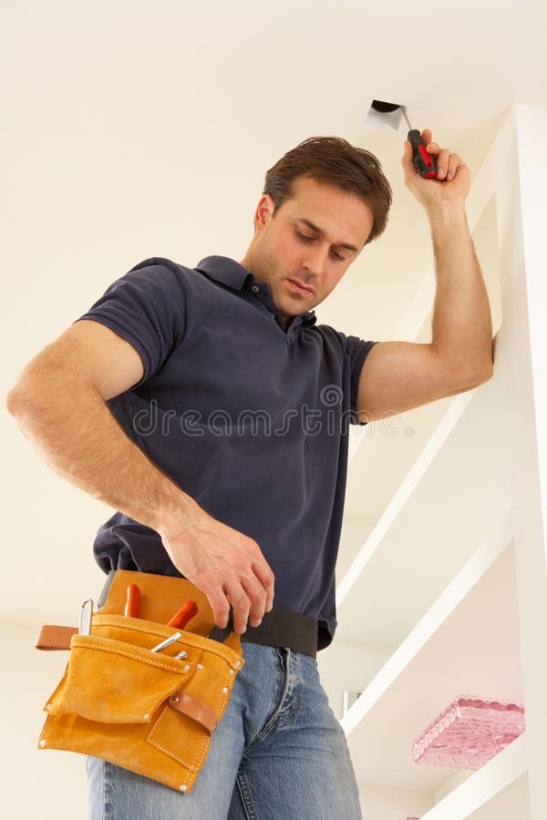 Electrician Installing Light Fitting. In Home stock photography