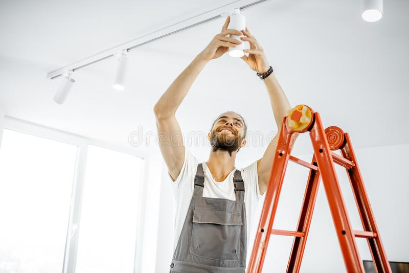 Electrician installing light at home. Repairman or professional electrician in workwear installing light spots, standing on the ladder in the white living room royalty free stock images