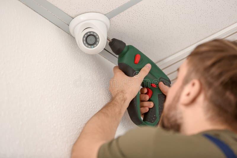 Electrician installing security camera indoors stock photos