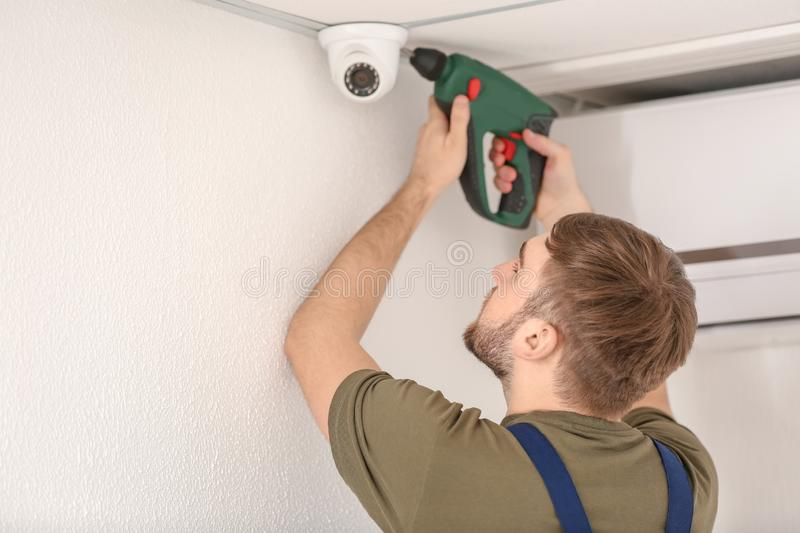Electrician installing security camera indoors stock photography