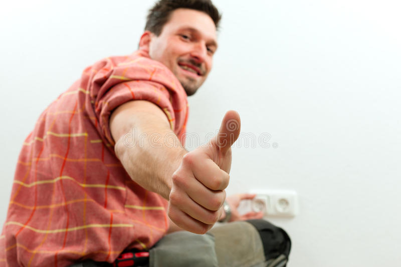 Electrician installing socket. Electrician installing a power socket, close-up royalty free stock photography