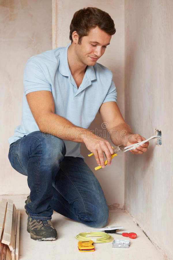 Electrician Installing Socket In New House. Electrician Installs Socket In New House stock photos