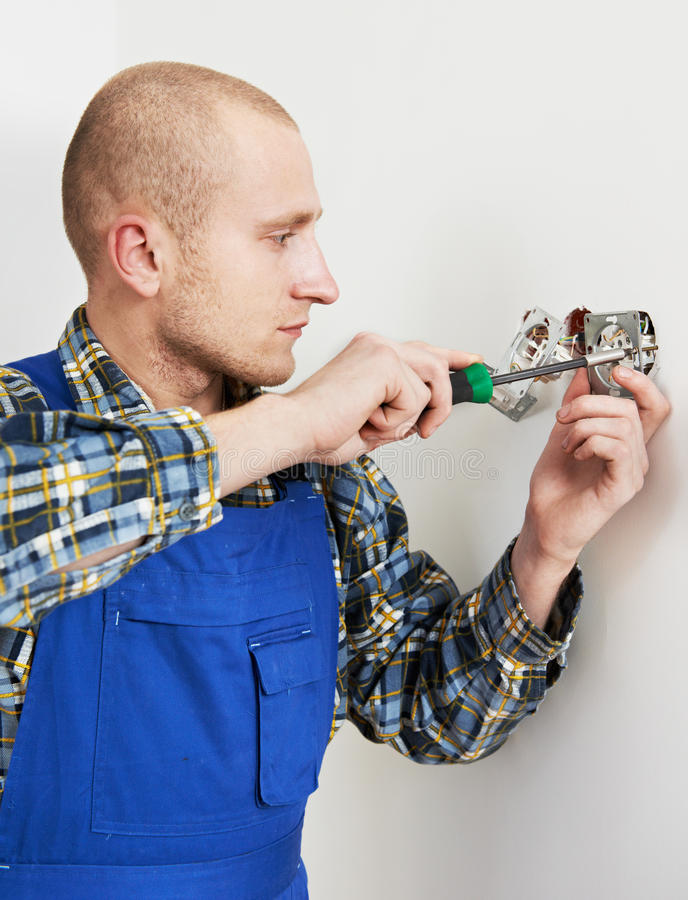 Electrician installing wall outlets. Young electrician at work with wall outlet and screwdriver installing sockets royalty free stock photos