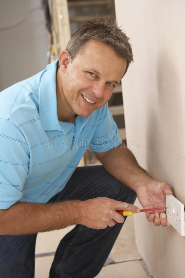 Electrician Installing Wall Socket. In House Build stock photography