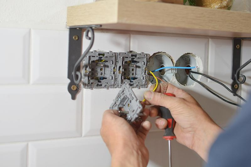 Electrician installing wall socket. In new building royalty free stock image