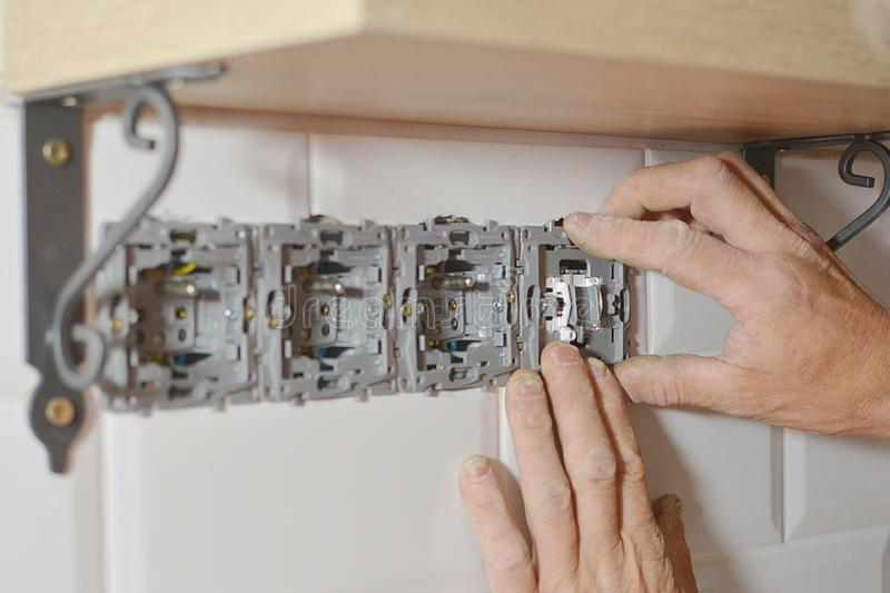 Electrician installing wall socket. In new building stock image
