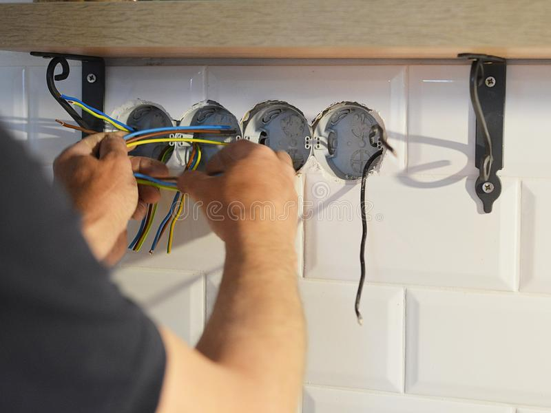 Electrician installing wall socket. In new building stock photos