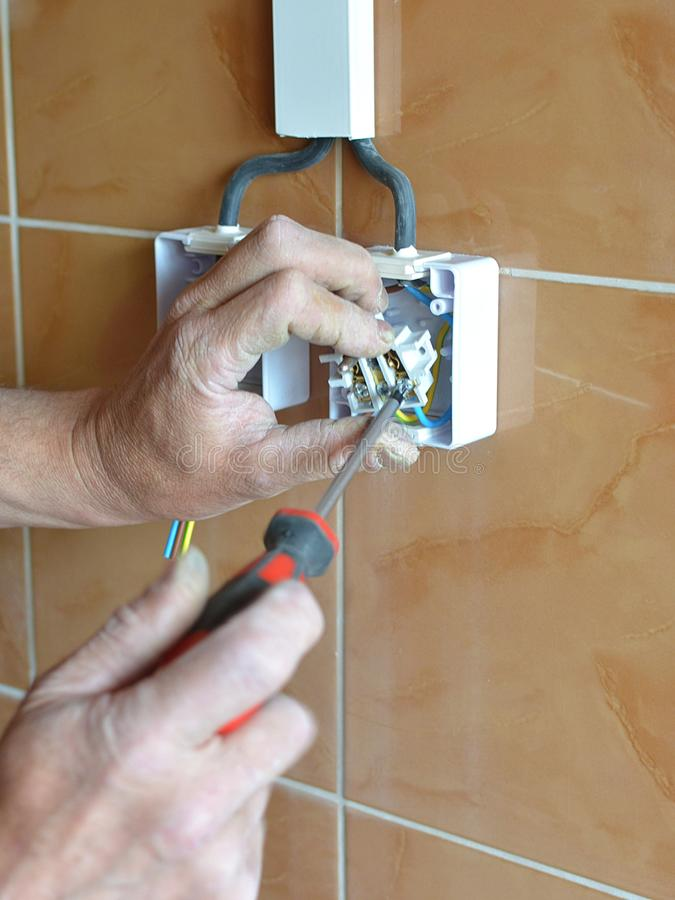Electrician installing wall socket in new building, stock photo