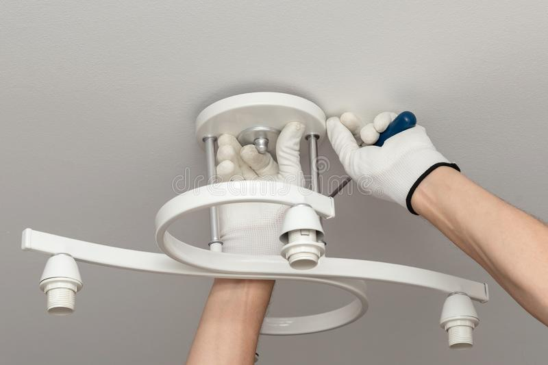 Electrician installs chandelier on the ceiling. Hands of worker in white gloves perform work with electricity in house. Electrician installs a white chandelier stock photography