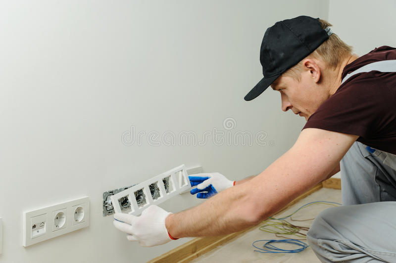 Electrician installs decorative frame. royalty free stock photo