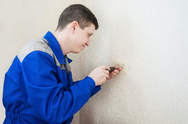 The electrician installs an electrical outlet stock images