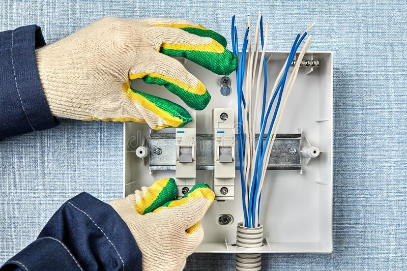 Electrician installs a household electrical panel stock photography