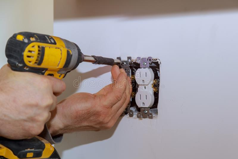 Electrician installs lighting switch in the wall stock photos
