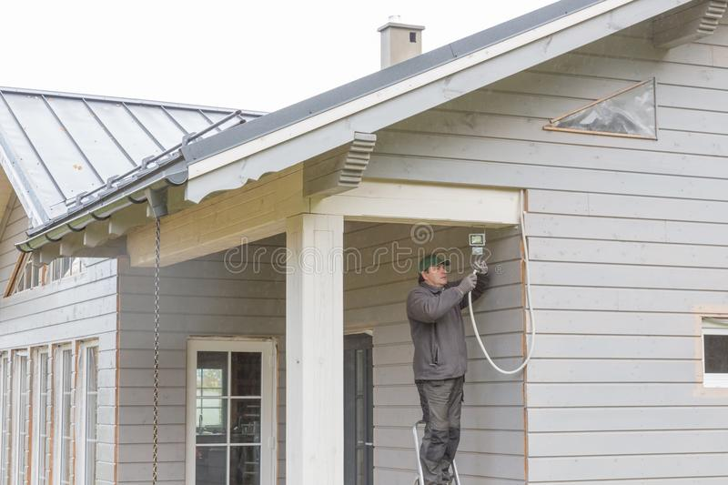 The electrician installs outdoor lighting, a lamp triggered by the motion on the wall of a beautiful wooden frame house, stock photo