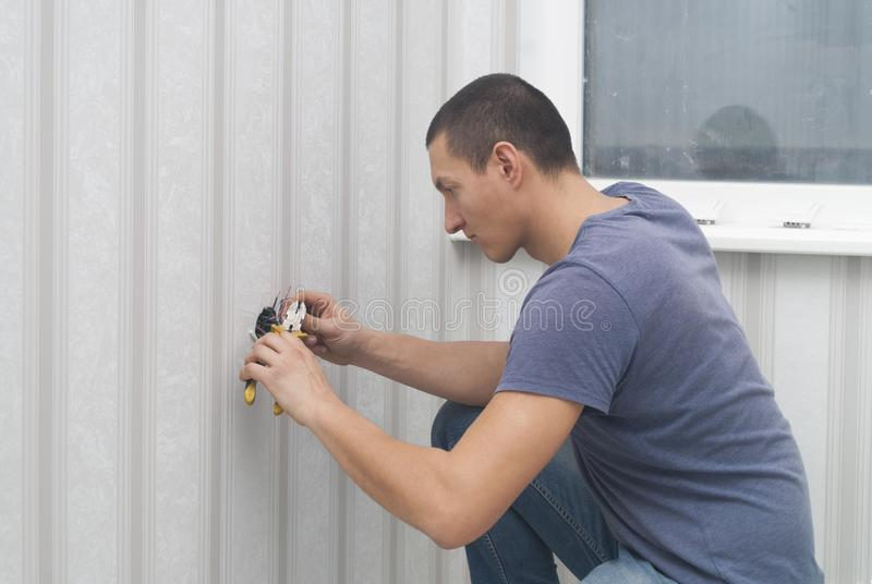 Electrician installs outlet stock photo