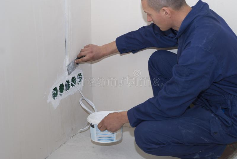 Electrician installs socket boxes. On the wall and puts a putty on them royalty free stock photos