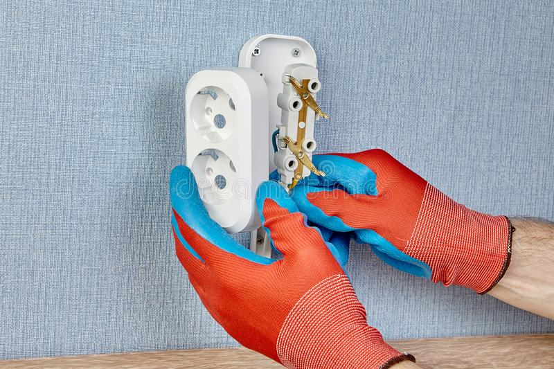 Electrician installs wall outlet royalty free stock photo