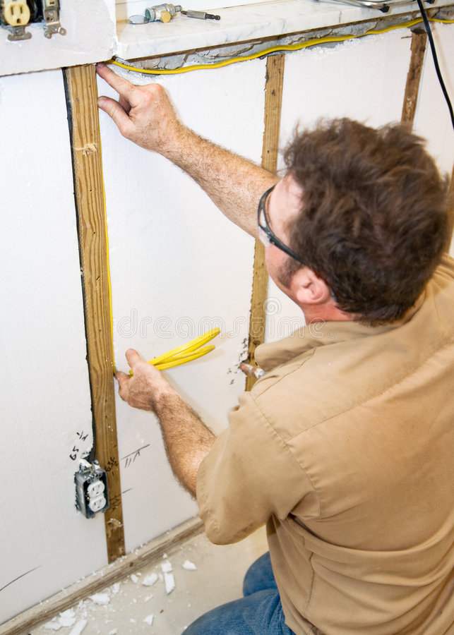 Electrician Installs Wiring in Wall. Electrician installing wiring in an interior wall. Authentic and accurate content depiction in accordance with industry code royalty free stock photos