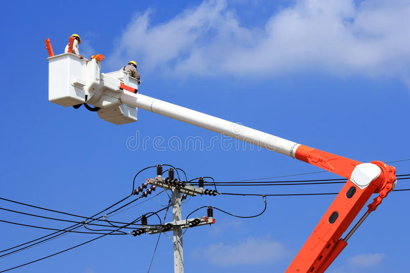 Electrician lineman on hydraulic platform royalty free stock image