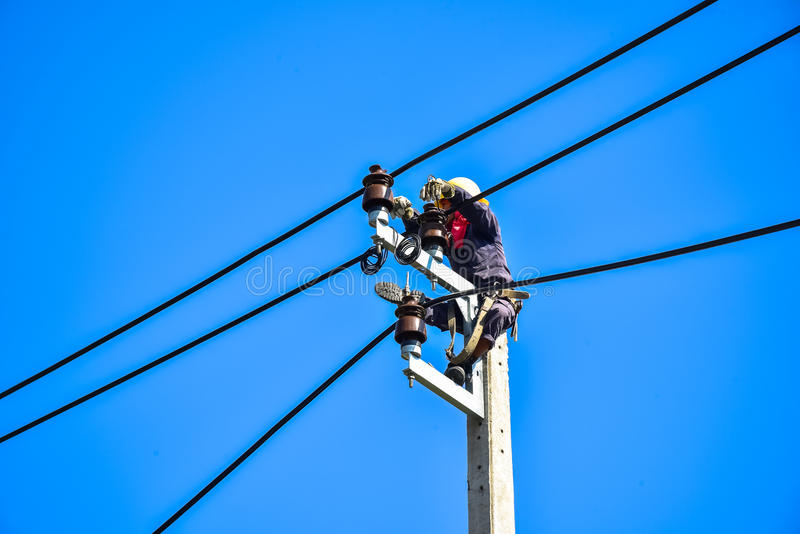 Electrician lineman repairing work on electric post power pole. Electrician perform maintenance on the transmission towers with use of claws- manholes and belt royalty free stock photo