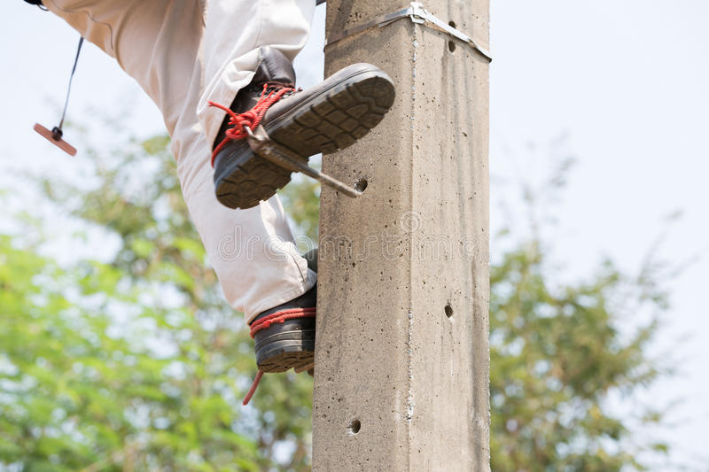 Electrician lineman repairman worker at climbing work on electric post power pole royalty free stock photos
