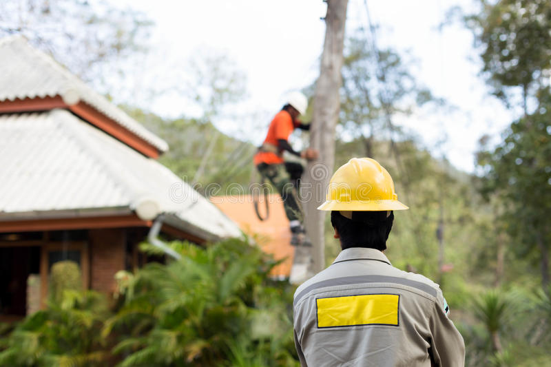 Electrician lineman repairman worker on electric post power pole royalty free stock photo